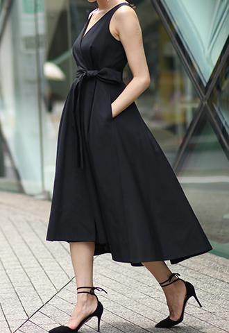 ブラックのノースリーブタイプのラップワンピース。深いタックを入れた前後で長さの違うスカートが特徴的な、ウエストリボンがスタイルアップしてくれるブラックのノースリーブタイプとなります。