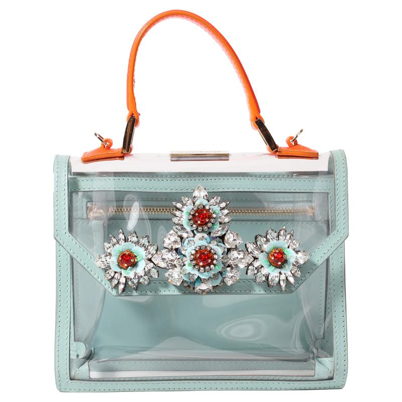 オレンジの持ち手に、ピンクのショルダーストラップ、水色で縁取られたクリアバッグ。フラワーモチーフのビジューが施されています。