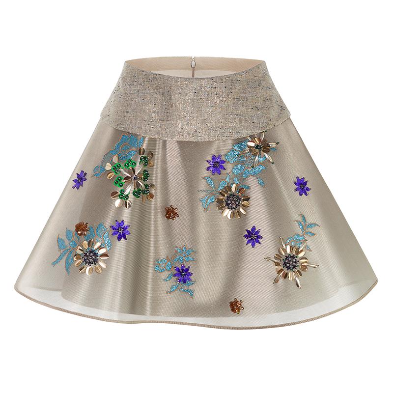 フラワーモチーフのビジューが施された、ハリ感のあるゴールドのミニ丈スカート